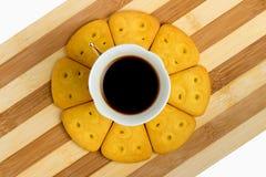 Een kop van espresso bevindt zich op een ronde die oppervlakte van koekjes op een gestreepte raad wordt gemaakt Mening van hierbo Stock Foto