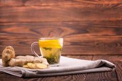Een kop van gele muntdrank Een theekopje op een donkere houten lijst Een mooie kop met gesneden citroen en organische gember De r Stock Foto's