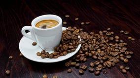 Een kop van hete koffie met geroosterde bonen rond op een zwarte achtergrond in 4k resolutie in langzame motie stock video