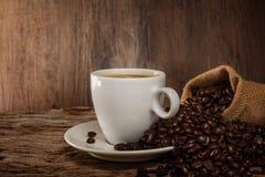 Een kop van hete koffie op een houten lijst met geroosterde koffiebonen Royalty-vrije Stock Afbeeldingen