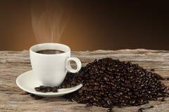 Een kop van hete koffie op een houten lijst met geroosterde koffiebonen Stock Fotografie