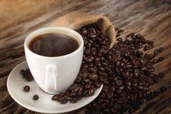 Een kop van hete koffie op een houten lijst met geroosterde koffiebonen Royalty-vrije Stock Foto's