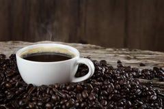 Een kop van hete koffie op een houten lijst met geroosterde koffiebonen Royalty-vrije Stock Foto