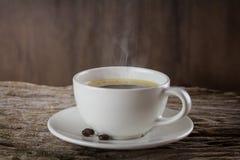 Een kop van hete koffie op een houten lijst met geroosterde koffiebonen Stock Foto