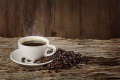 Een kop van hete koffie op een houten lijst met geroosterde koffiebonen Royalty-vrije Stock Afbeelding