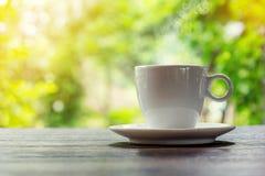 Een kop van hete koffie op een houten lijst in een tuin Royalty-vrije Stock Foto's
