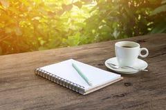Een kop van hete koffie op een houten lijst in een tuin Royalty-vrije Stock Afbeelding