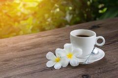 Een kop van hete koffie op een houten lijst in een tuin Stock Afbeelding