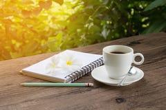 Een kop van hete koffie op een houten lijst in een tuin Royalty-vrije Stock Foto