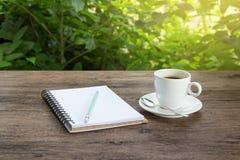 Een kop van hete koffie op een houten lijst in een tuin Stock Fotografie