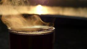 Een kop van hete koffie op een meerbank bij een schitterende zonsondergang in langzame motie stock video