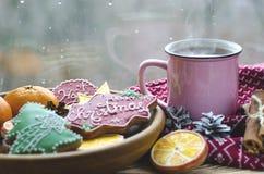 Een kop van hete thee bevindt zich op een houten lijst naast een houten die plaat waarop peperkoekkoekjes van sinaasappel worden  royalty-vrije stock afbeelding