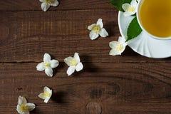 Een kop van jasmijnthee met jasmijn bloeit op een houten achtergrond Stock Foto's