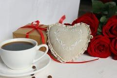 Een Kop van koffie, een boeket van rode rozen en een gift met een rood lint op het lijstclose-up stock foto's