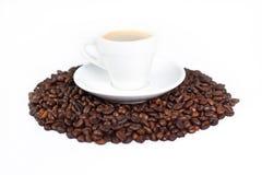 Een kop van koffie bovenop koffiebonen royalty-vrije stock afbeeldingen