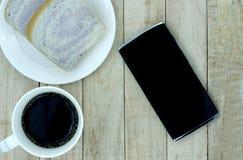 Een kop van koffie, brood op witte plaat, smartphone op hout backgr royalty-vrije stock foto's