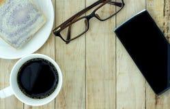 Een kop van koffie, brood op witte plaat, smartphone op hout backgr stock afbeelding