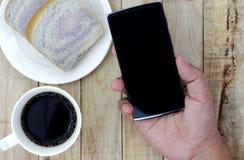 Een kop van koffie, brood op witte plaat, smartphone streeft ter beschikking na stock afbeelding