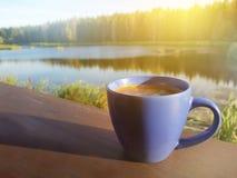 Een kop van koffie door een meer in de ochtend Weergeven van het huis van het land royalty-vrije stock foto