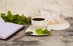 Een kop van koffie, een hoed en een notitieboekje Royalty-vrije Stock Foto's