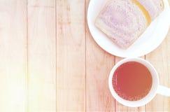 Een kop van koffie en brood op witte plaat op houten achtergrond stock fotografie