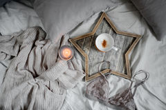Een kop van koffie en een kaars in een Skandinavisch houten dienblad in een comfortabel bed met hoofdkussens royalty-vrije stock foto