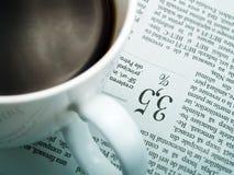 Een kop van koffie en een krant Stock Afbeelding