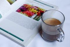 Een kop van koffie en een fotografisch boek royalty-vrije stock afbeeldingen