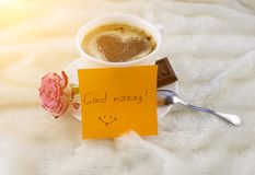 Een kop van koffie en een hart maakte van kaneel, een roos, een chocolade en een sticker met een sticker van de goedemorgeninschr stock foto