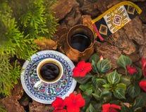 Een kop van koffie en jezva bevinden zich onder de bloemen in de tuin stock foto