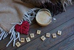 Een kop van koffie en een rood hart dichtbij een wollen deken op de lijst met een woord van houten brieven zoet huis royalty-vrije stock foto