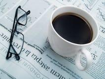 Een kop van koffie, glazen en een krant Stock Foto