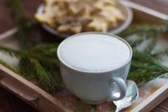 Een Kop van koffie met een dik schuim en Kerstmiskoekjes met suiker en kaneel stock afbeelding