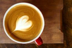 Een kop van koffie met hart latte art. stock afbeeldingen
