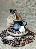 Een kop van koffie met koffiebonen stock fotografie