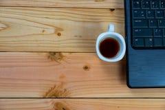 een kop van koffie met labtop op houten bureau stock foto