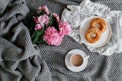 Een kop van koffie met snoepjes en pioenen op een grijze achtergrond Stock Foto
