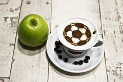 Een kop van koffie met voetbalbal Stock Fotografie