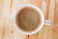 Een kop van koffie met in een witte kop op houten achtergrond Stock Foto