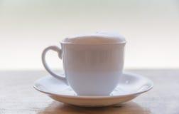 Een kop van koffie met in een witte kop op houten achtergrond Stock Fotografie
