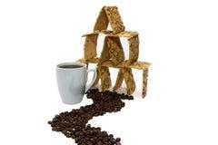 Een kop van koffie naast het koekjeshuis, de weg van de korrels van de koffie royalty-vrije stock afbeeldingen