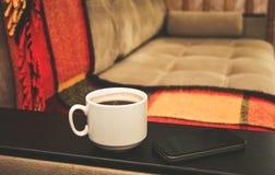 Een kop van koffie is op de banklijst, daarna is een mobiele telefoon, huiscomfort stock fotografie