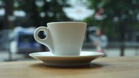 Een kop van koffie op een lijst in een koffie door het venster op de achtergrond van mensen en auto's stock video