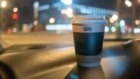 Een kop van koffie is op het dashboard van de auto Royalty-vrije Stock Afbeeldingen
