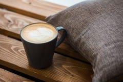 Een kop van koffie op een houten achtergrond met een grijs hoofdkussen, Koffietijd royalty-vrije stock afbeeldingen