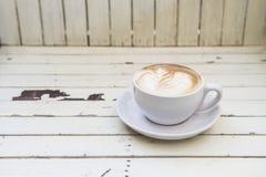 Een kop van koffie op houten lijst Stock Afbeelding