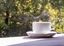 Een kop van koffie op een houten lijst tegen de achtergrond van de herfstaard Stock Foto