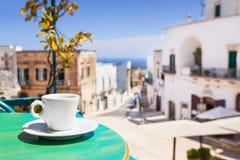 Een kop van koffie op lijst met Italiaanse stad bij de achtergrond Stock Foto
