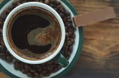 Een kop van koffie op een schotel met geroosterde koffiebonen en een stuk van chocolade royalty-vrije stock fotografie