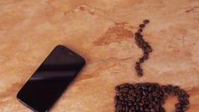 Een kop van koffiebonen en een mobiele telefoon Op de keuken marmeren lijst het teken van een kop koffiebonen en mobiel stock videobeelden